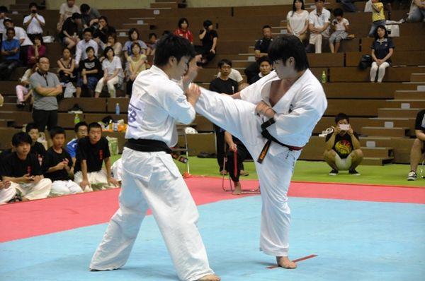 立石(左)は左右の廻し蹴り・鍵突き・下突きで揺さぶりを掛ける。岡田(左)はこれを凌ぎ、縦形の技に加え下段蹴りを有効に使い、一進一退の攻防が展開した。