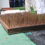 ラミンダ・ペレラ支部長が4インチの釘が一面に打ち込まれた板の上に横たわり、その腹の上で100kgの石をハンマーで割る